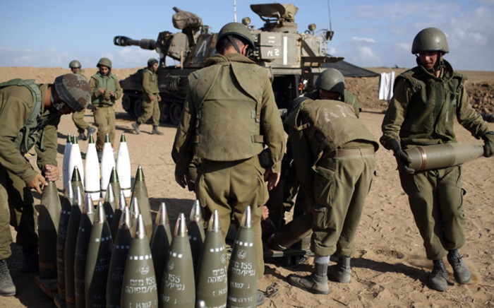 FILE: Israeli soldiers organise 155mm shells near the Israeli border with the Gaza Strip, on 17 July, 2014. Picture: AFP.