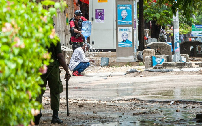 A member of Tanzanian Security Forces empties a bucket of water on a man in Stone Town, Zanzibar, on 27 October 2020.Picture: AFP.