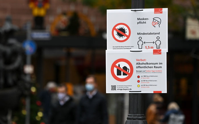 An information poster on the wearing of face masks and social distancing measures as well as the ban of alcoholic beverages during certain hours during the novel coronavirus pandemic is seen in the city of Nuremberg, southern Germany, on 28 October 2020. Picture: AFP