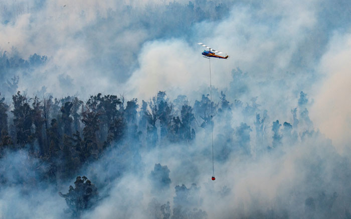 This handout photo taken on 29 December 2019 and received on 30 December from Victoria's Department of Environment, Land, Water and Planning (DELWP) shows a helicopter dumping water on a fire in Victoria's East Gippsland region. Picture: AFP