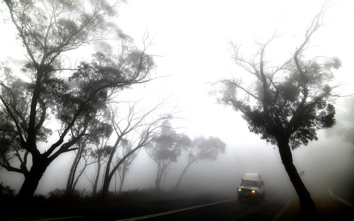 FILE: A car makes its way through thick fog mixed with bushfire smoke in the Ruined Castle area of the Blue Mountains, some 75 kilometres from Sydney, on 11 January 2020. Picture: AFP