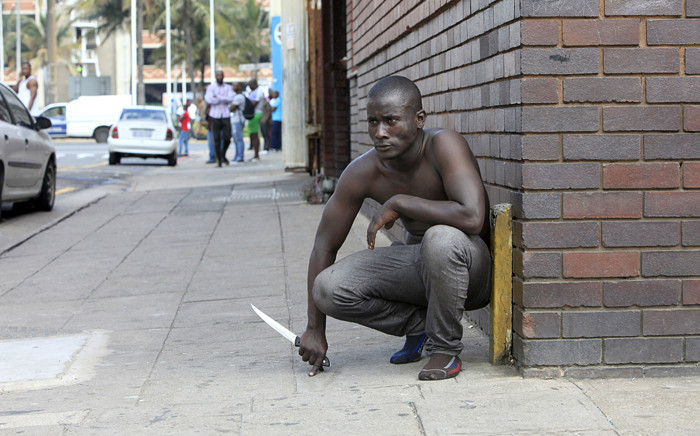 A foreign national holds a knife following clashes between a group of locals and police in Durban on 14 April, 2015 amidst ongoing violence against foreign nationals living in Durban. Picture: AFP.