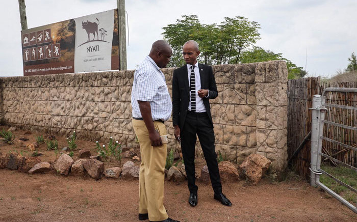 The SAHRC's Buang Jones (right) with a SAPS official discussing the commission's right to enter the Nyati Bush and Riverbreak resort in Brits on 21 January 2020. Picture: Abigail Javier/EWN