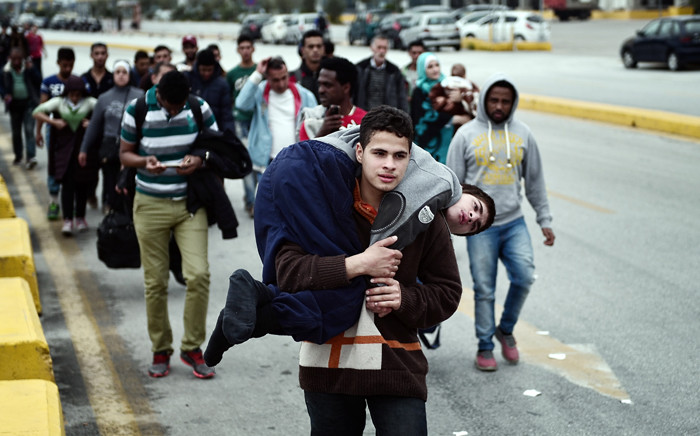 A Syrian man carries his disabled relative as they walk with other migrants and asylum seekers to find transportation to central Athens or continue towards the Greek-Macedonian border from the port of Piraeus on 21 October, 2015. Picture: AFP.