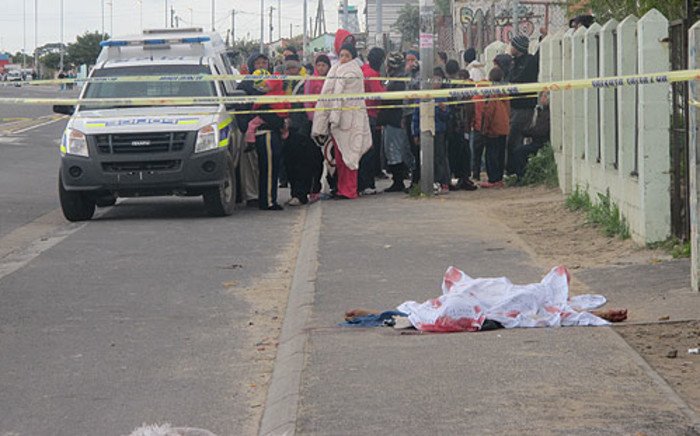 Community members watch on after a 37-year-old man was shot dead in Wesbank on 10 July 2012. Picture: Chané Fortuin/EWN