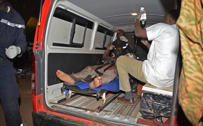 A wounded man receives medical care outside the Splendid hotel during an attack on both the hotel and a restaurant by Al-Qaeda linked gunmen late on January 15, 2016 in Ouagadougou. Burkina Faso troops supported by French special forces were battling Al-Qaeda linked gunmen in the early hours of January 16 in a Ouagadougou hotel where at least 20 people have been killed. Picture: AFP.