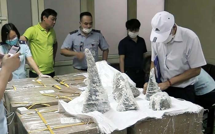 This picture from the Vietnam News Agency released on 27 July 2019 shows customs officials at Noi Bai International Airport removing smuggled rhino horn pieces from packaging in Hanoi. Picture: AFP.