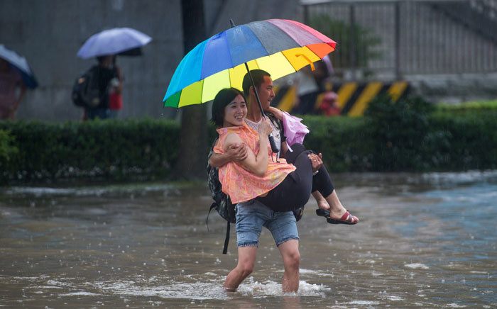 FILE: This picture taken on 2 July 2016 shows people crossing a flooded street in Wuhan, in China's central Hubei province. Picture: STR/AFP.