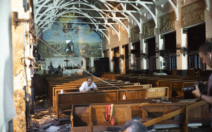 FILE: Journalists take pictures inside St. Anthony's Shrine in Colombo on April 26, 2019, following a series of bomb blasts targeting churches and luxury hotels on Easter Sunday in Sri Lanka. Picture: AFP