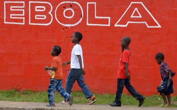 A file photo taken on 31 August, 2014 shows children walking past a slogan painted on a wall reading 'Ebola' in Monrovia. Picture: AFP