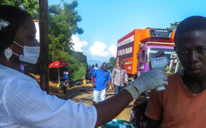 A Sierra Leone health worker takes the temperature of a man at a checkpoint in Port Loko district, one of the hardest hit areas due to the Ebola virus on 25 October 2014. Picture: EPA.
