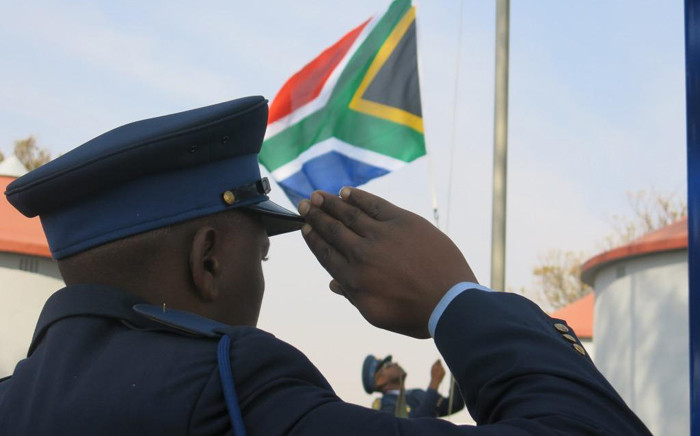 FILE: One of the police trainees salute as the South African flag is raised during a graduation parade. Picture: SAPS