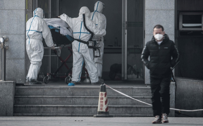 FILE: Medical staff members carry a patient into the Jinyintan hospital, where patients infected by a mysterious SARS-like virus are being treated, in Wuhan in China's central Hubei province on January 18, 2020. Picture: AFP.