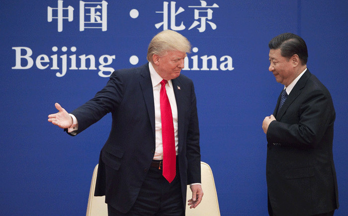 FILE: US President Donald Trump (L) gestures next to China's President Xi Jinping during a business leaders event at the Great Hall of the People in Beijing on 9 November 2017. Picture: AFP