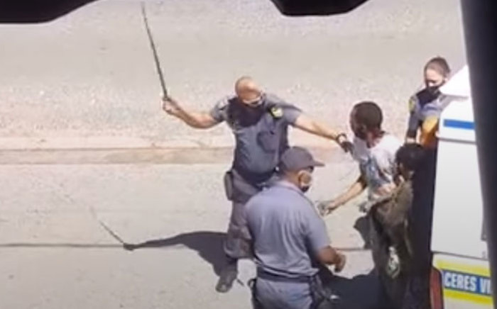 A screengrab of a police officer assaulting a man with a sjambok in Worcester: Picture: SAPS
