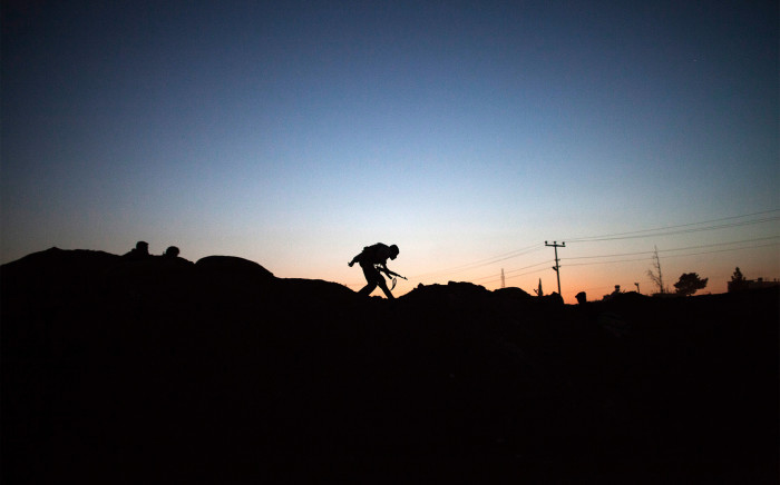 FILE: The silhouette of an armed fighter of the Committees for the Protection of the Kurdish People (YPG) is seen as he runs to take position along the front line.
