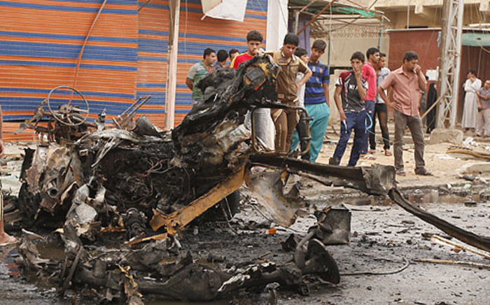 Iraqis look at the remains of a car bomb that detonated in the Kamaliya area of eastern Baghdad. Picture: AFP