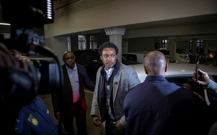 Duduzane Zuma is escorted into the Commercial Crimes Court by police. Picture: Thomas Holder/EWN.