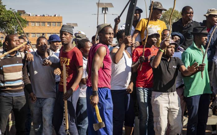 Hostel dwellers in Jeppestown gather before Bheki Cele arrives to address them on 3 September 2019. Picture: Thomas Holder/EWN