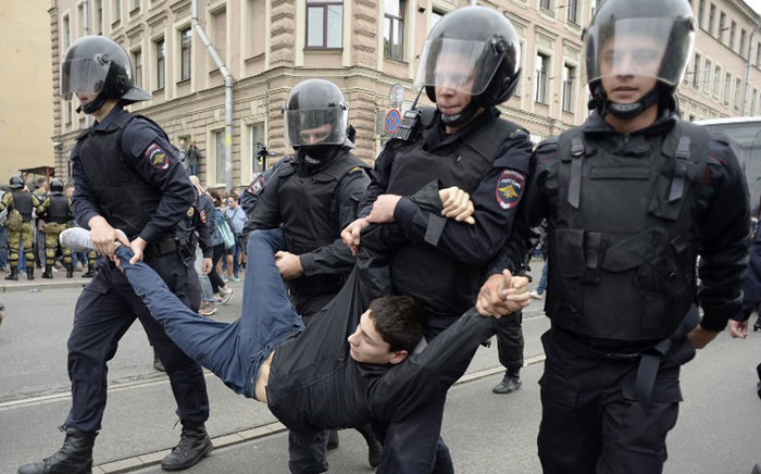 Police officers detain a young man during a protest rally against planned increases to the nationwide pension age in Saint Petersburg on 9 September 2018. Picture: AFP.