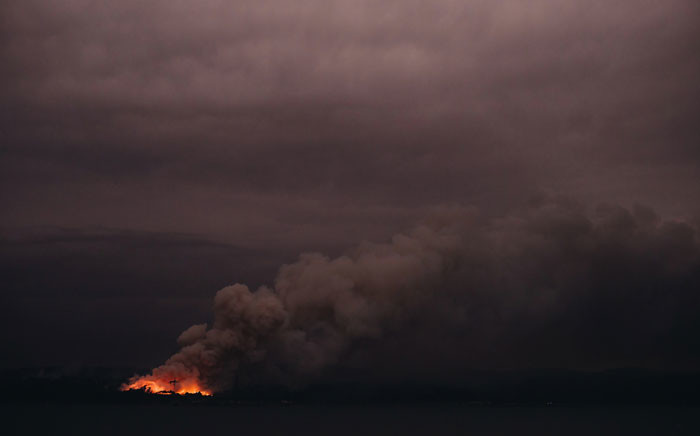 This handout photo taken on 6 January 2020 and received on 7 January from the Australian Department of Defence shows a fire in the distance seen from the Royal Australian Navy's HMAS Adelaide ship off the coast in Eden in New South Wales, as part of bushfire relief operations. Picture: AFP
