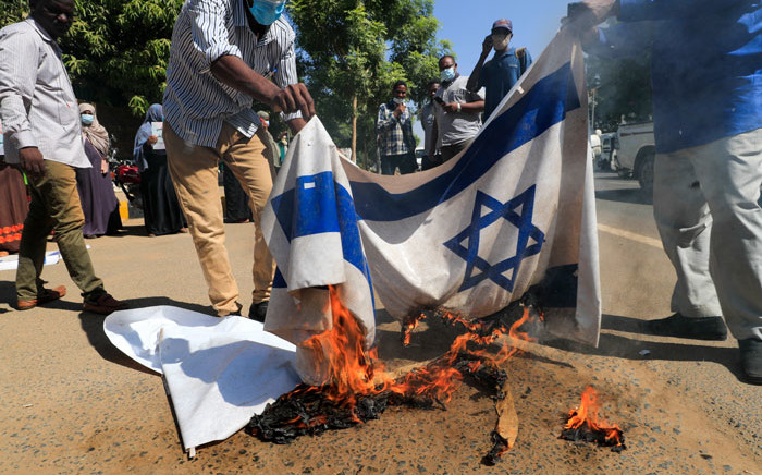 Sudanese demonstrators burn Israeli flags during a rally against their country's recent signing of a deal on normalising relations with the Jewish state, outside the cabinet offices in the capital Khartoum, on 17 January 2021. Picture: Ashraf Shazly/AFP