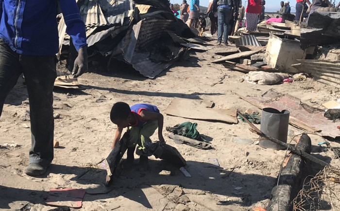 A young boy lends a hand as Overcome Heights informal settlement residents start cleaning up following a fire that gutted about 500 shacks. Picture: Lauren Isaacs/EWN