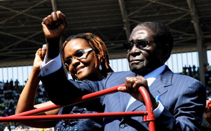 Zimbabwean President Robert Mugabe (R), accompanied by wife Grace, raises his fist as he greets the crowd at his inauguration ceremony in Harare on 22 August, 2013. Picture: AFP.