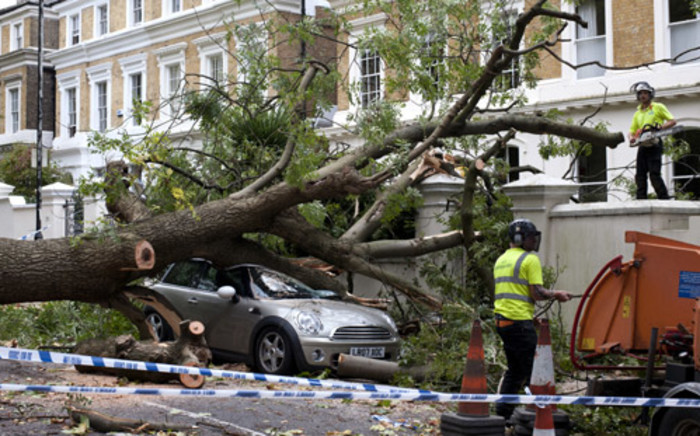 Contractors work on clearing the debris after a tree fell on car during a storm in London on 28 October, 2013. Picture:AFP