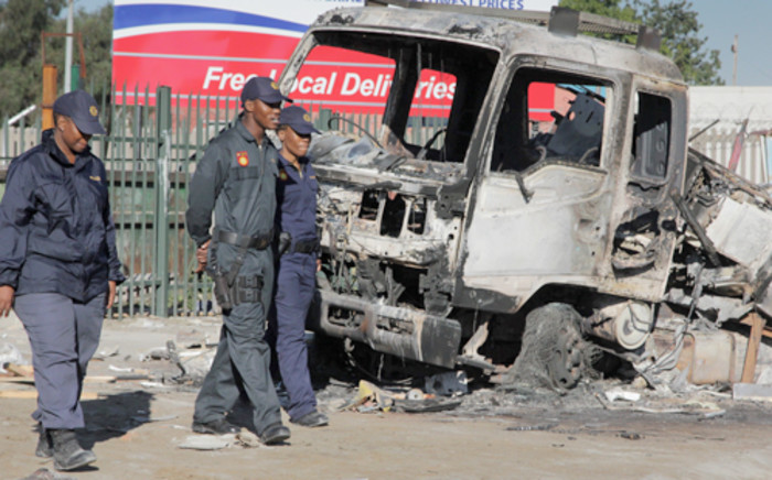 Police officers pass a burnt out truck in the Zamdela informal settlement in Sasolburg after residents went on the rampage on 21 January 2013. Picture: Sebabatso Mosamo/EWN.