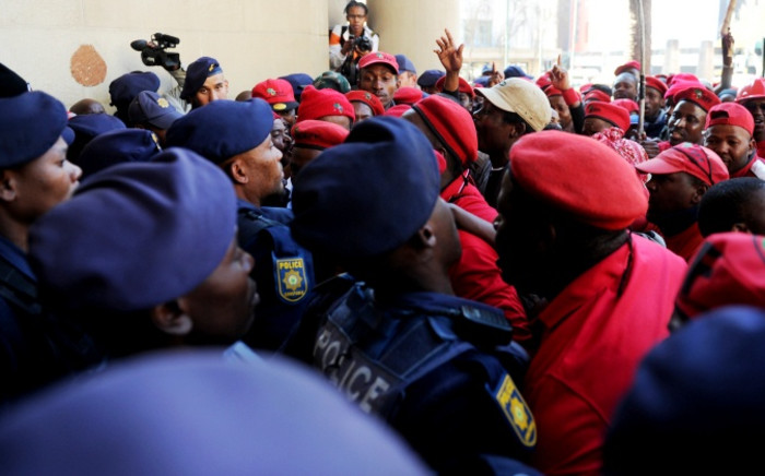 EFF push their way past policemen into the Gauteng Provincial Legislature in Johannesburg during a protest march on 22 July 2014. Picture: Sapa.