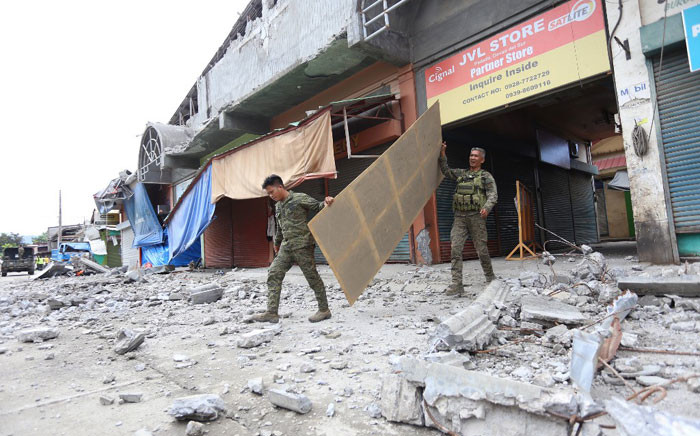 Soldiers walk among debris in Padada town, Davao del Sur province on the southern island of Mindanao on 16 December 2019, following a 6.8-magnitude earthquake on 15 December 2019. Picture: AFP
