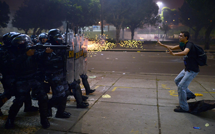 A demonstrator is shot by rubber bullets as anti riot police officers charge after clashes erupted during a protest against corruption and price hikes, on June 20, 2013, in Rio de Janeiro. Brazilians took to the streets again Thursday in several cities on a new day of mass nationwide protests, demanding better public services and bemoaning massive spending to stage the World Cup.      AFP PHOTO / CHRISTOPHE SIMON