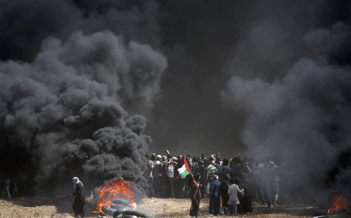 FILE: A Palestinian holds his national flag in the smoke billowing from burning tyres during clashes with Israeli forces near the border between the Gaza strip and Israel east of Gaza City on 14 May 2018. Picture: AFP