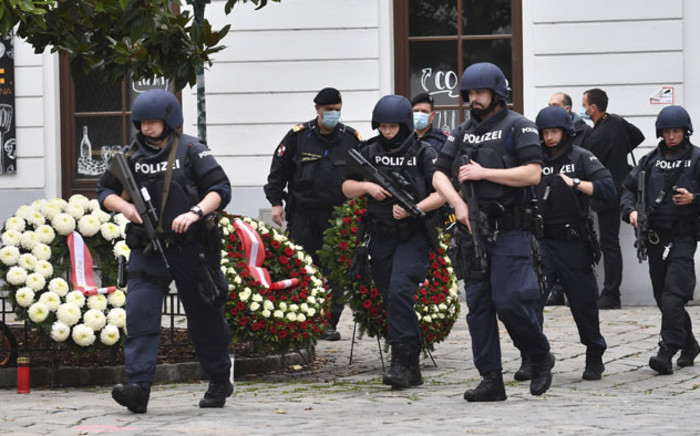 Policemen walk past wreaths placed at a crime scene before the arrival of the Austrian Chancellor, who paid his respects to the victims of a shooting, in Vienna on 3 November 2020, one day after the shooting at multiple locations across central Vienna. Picture: AFP