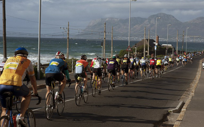 A group of riders ride through Muizenburg, with False Bay in the background in the Cape Town Cycle Tour in March, 2014. Picture: AFP