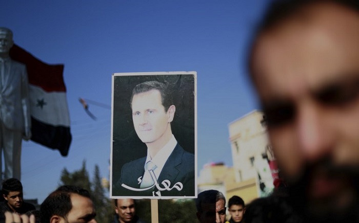 Syrian demonstrators hold a portrait of President Bashar al-Assad during a demonstration in the northeastern Syrian Kurdish-majority city of Qamishli on 23 December, 2018, asking for the Syrian army's protection as Turkey threatens to carry out a fresh offensive following the US decision to withdraw their troops. Picture: AFP