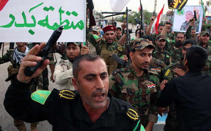 Members of Shiite factions hold banners and flags during a demonstration to protest against the Saudi-led Arab coalition which is carrying out air strikes on Huthi militia targets across Yemen on 31 March, 2015 in the mainly Shiite southern Iraqi city of Basra. Picture: AFP.