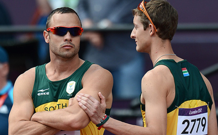 Oscar Pistorius and Willie de Beer before the 4x400m relay race. Picture: AFP
