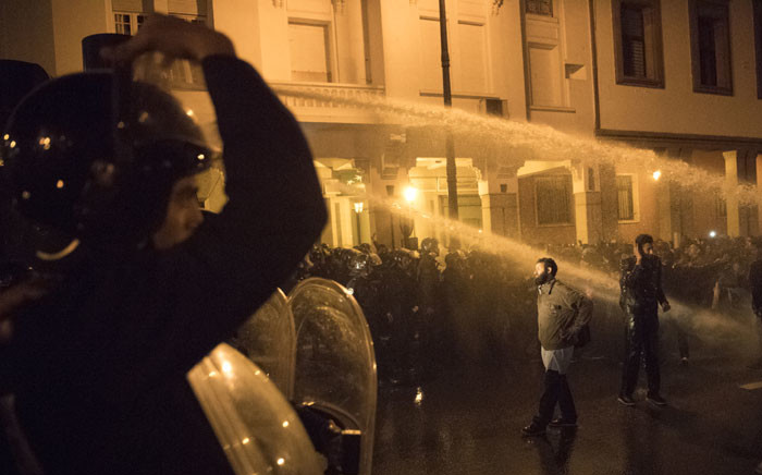 Moroccan protesters stand in front of water cannons used by the police during a demonstration in the capital Rabat on 24 March 2019. Picture: AFP