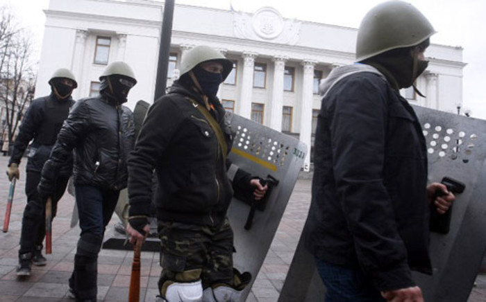 FILE: Maidan self-defence activists stand guard outside the parliament in Kiev during a session on February 22, 2014. Picture: AFP.