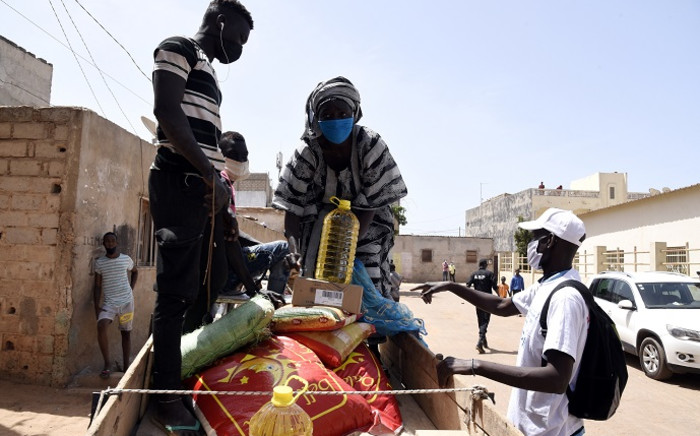FILE: Beneficiaries of food parcels load their good onto a horse cart during the launch of the distribution of food at the Guinaw Rails cultural center in Pikine on 28 April 2020. Senegal kicked off a massive food distribution operation to help nearly half of its population cope with the consequences of the COVID-19 pandemic, which is slowing down the economy of this West African country. Picture: AFP