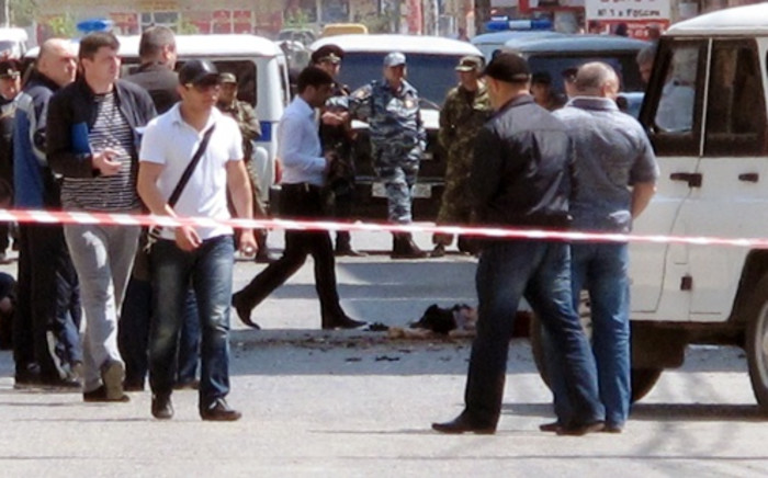 FILE:Investigators work at the site of a streetside bomb blast in Makhachkala, the capital of Russia's volatile Dagestan region, on 1 May, 2013. Picture:AFP
