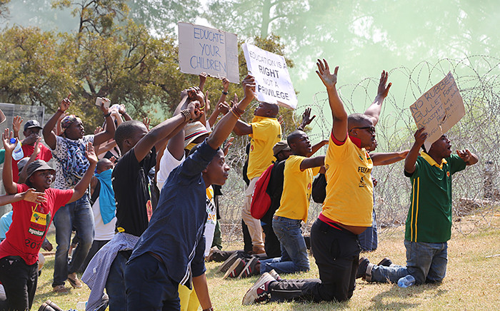 As tear gas fills the air at the Union Buildings in Pretoria, students put their hands in the air as a sign of surrender to police who they clashed with during protests on 23 October 2015 over proposed university fee increases. Picture: Reinart Toerien/EWN