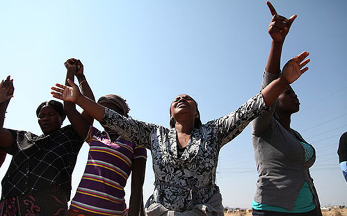 A congregation holds a prayer session at the scene of the Lonmin's Marikana shooting on 19 August 2012. Picture: EWN