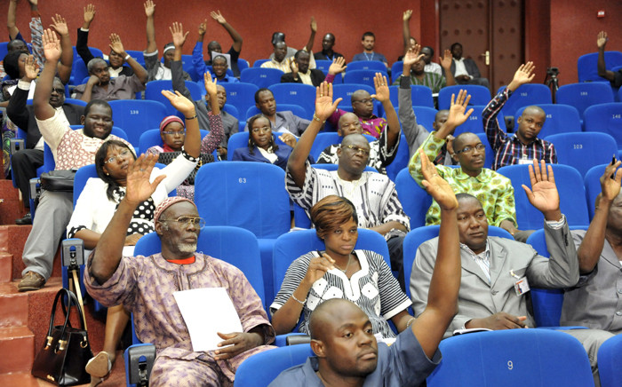 Members of Burkina Faso's interim parliament raise their hands on 16 July, 2015 in Ouagadougou as they vote on a resolution asking the High Court to put deposed leader Blaise Compaore on trial for high treason and violating the constitution. Picture: AFP.