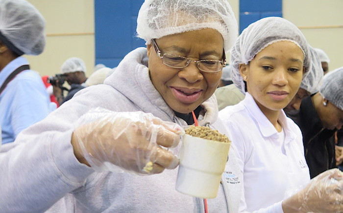 Graca Machel helps to package 1-million meals at the Stop Hunger Now Nelson Mandela 67-minute initiative. Picture: Louise McAuliffe/EWN.