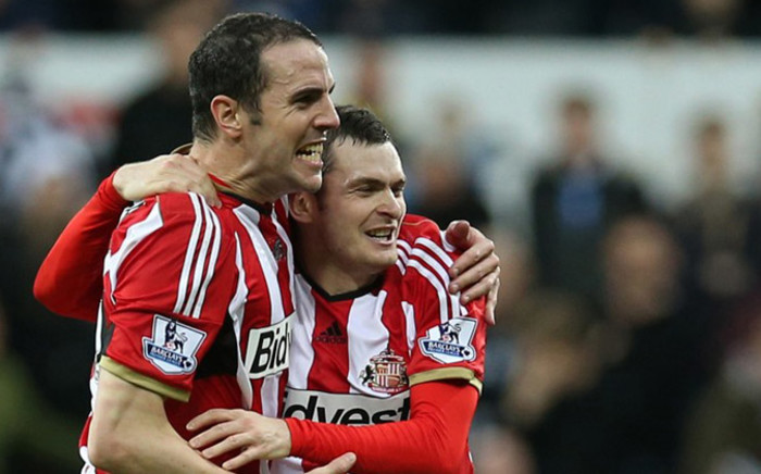 Sunderland's Irish defender John O'Shea (L) celebrates at the final whistle with goal-scorer, Sunderland's English midfielder Adam Johnson after the English Premier League football match between Newcastle United and Sunderland at St James' Park in Newcastle-upon-Tyne, north east England, on 21 December, 2014. Picture: AFP