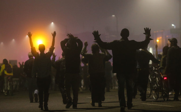 Protesters walk thorugh fog with their hands raised during demonstrations following a grand jury's decision not to indict a police officer in the chokehold death of Eric Garner on 4 December, 2014. Picture: AF