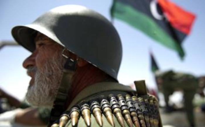 A Libyan rebel fighter wearing an ammunition belt waits in a staging area Ajdabiya on April 14, 2011. Picture: AFP